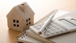 como-definir-o-valor-do-aluguel - uma miniatura de casa com calculadora