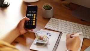 aluguel-no-imposto-de-renda uma mão segurando calculadora dinheiro em cima de um caderno e outra mão anotando com caneta no caderno