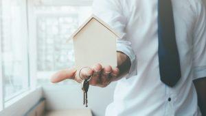 sucesso-da-imobiliária - homem segurando miniatura de casa com uma chave